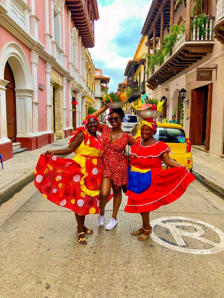 Black female traveler in Cartagena, Colombia, with two local woman wearing fruit bowls on their heads.